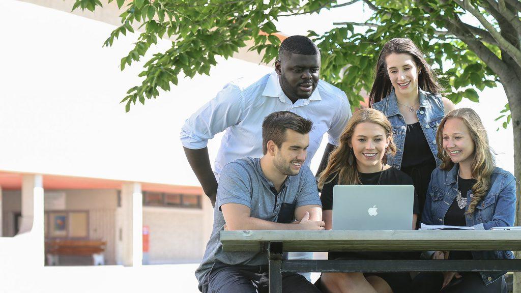 5 étudiants du Cégep de Thetford devant un ordinateur portable